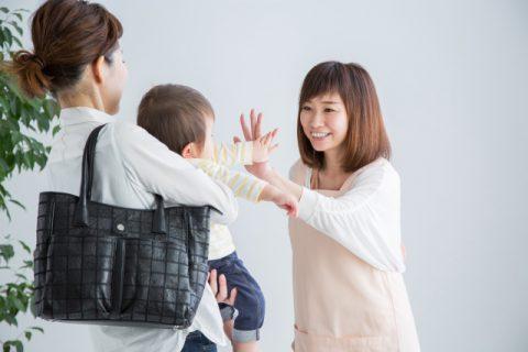 子供を見送る保育士の女性
