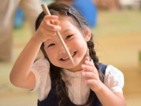 箸を持つ幼稚園の女の子