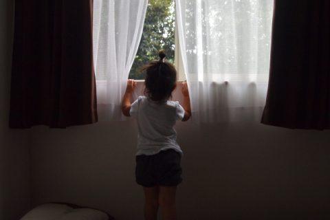 窓の外を寂しそうにみる女の子