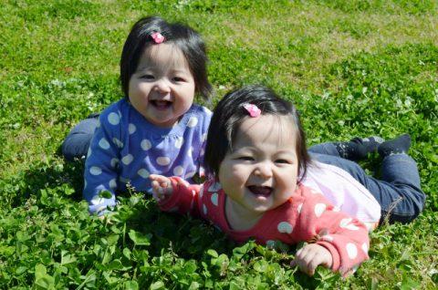 双子の赤ちゃんが芝生で寝そべる