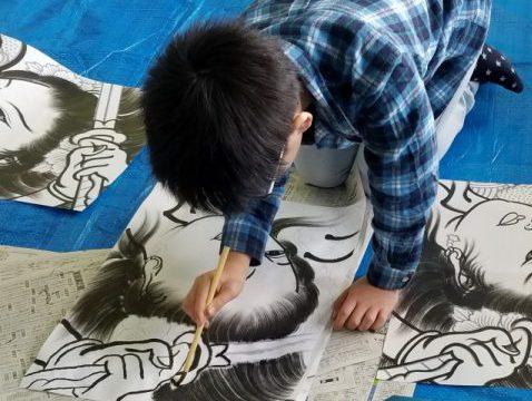 墨汁で日本画を書く子供