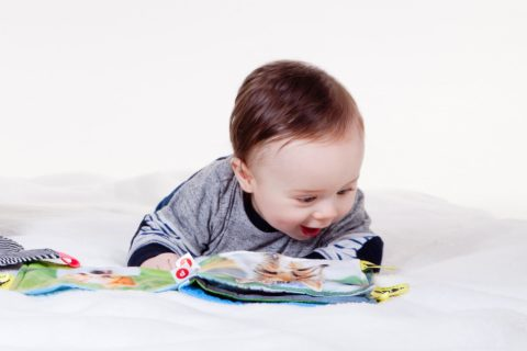 絵本をうれしそうに見る赤ちゃん