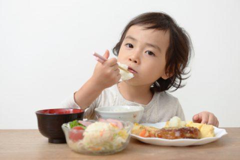 お箸で食事をする女の子
