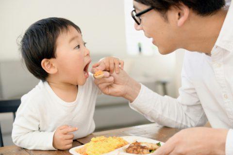パパにスプーンで食べさせてもらう男の子