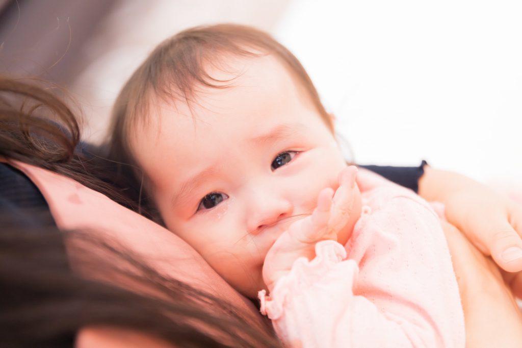 ママに抱っこをされてなく赤ちゃん