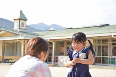 幼稚園で泣いている赤ちゃんと先生