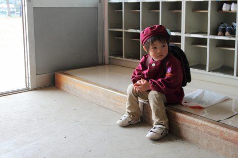 幼稚園の玄関に座る子供