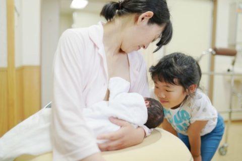 母乳を飲ませるママと飲む赤ちゃん。それを見るお姉ちゃん