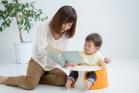 赤ちゃんに絵本を読む保育士