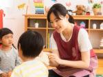 子供に絵本を読む保育士