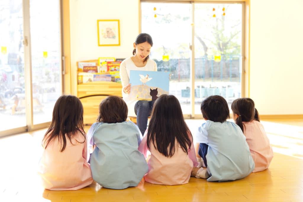 絵本を読む保育士とみる子供達