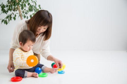赤ちゃんとおもちゃで遊ぶ保育士