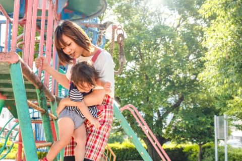 子供を遊具で抱っこする保育士