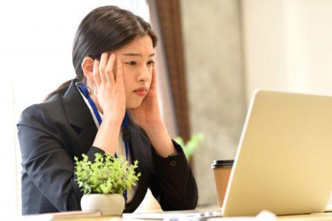 パソコンを見つめるスーツの女性