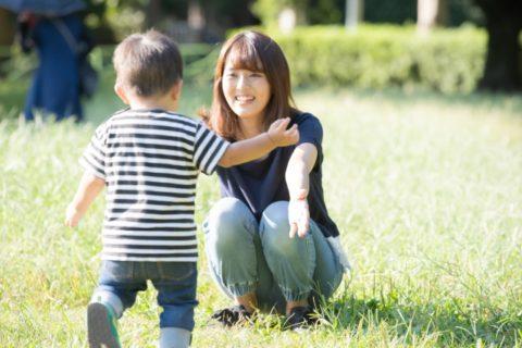 芝生でママに向かって走る2歳児