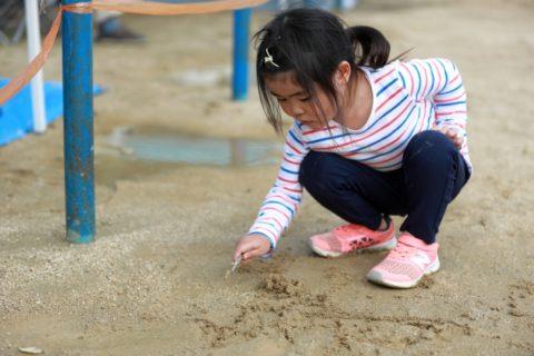 砂にお絵描きをする女の子