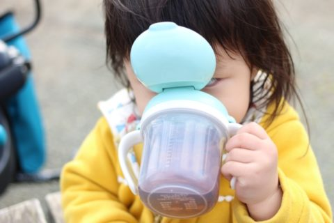 マグでお茶を飲む赤ちゃん