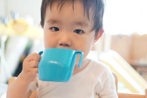 麦茶をコップで飲む赤ちゃん