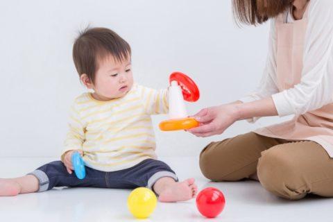 おもちゃで遊ぶ赤ちゃんと女性保育士