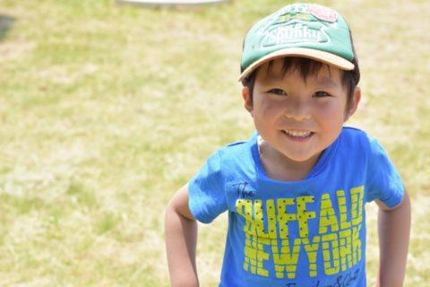 帽子をかぶった男の子が芝生で遊ぶ