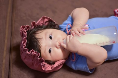 哺乳瓶を持つ赤ちゃん