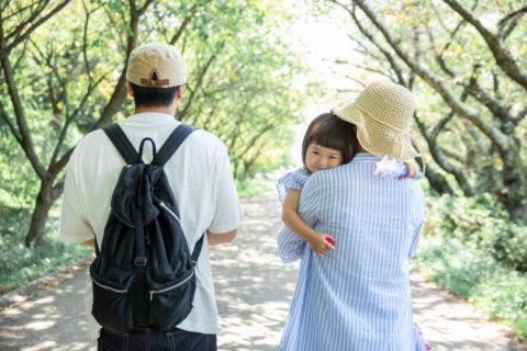 赤ちゃんを抱っこするママと一緒に歩くお父さん
