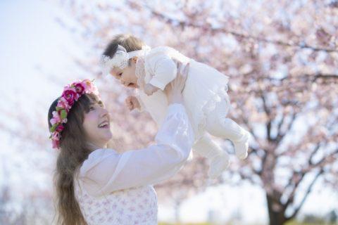 桜の下で赤ちゃんを抱っこするママ