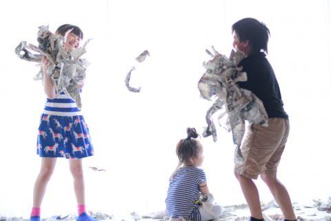 新聞で遊ぶ子供たち