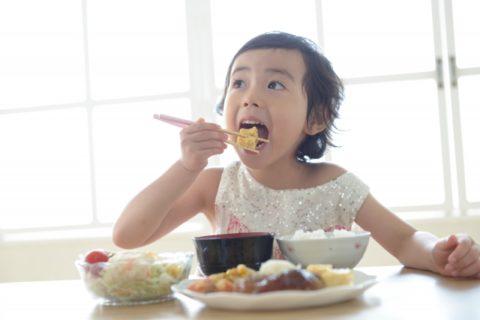 お箸で食べる女の子