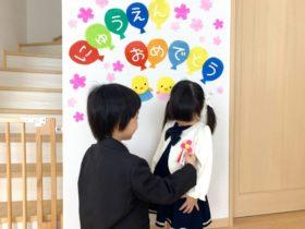 入園式の看板の前に立つママと子供
