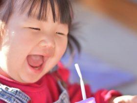 ストローを咥える笑顔の赤ちゃん
