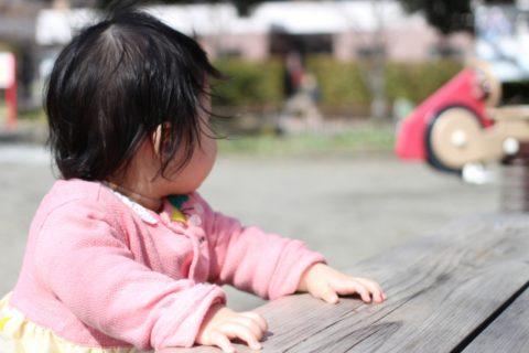 公園でつかまり立ちをする赤ちゃん