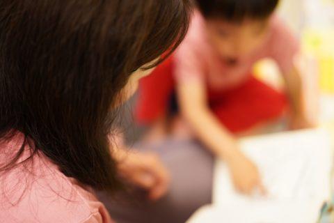絵本を見る子供と見守る女性