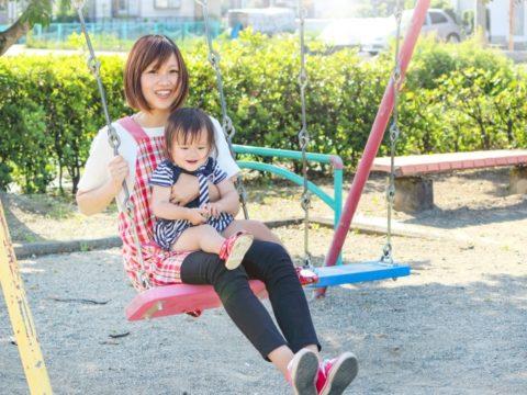 ブランコに子供と一緒に乗る保育士