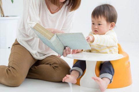 絵本を子供に読む保育士