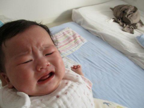 布団で泣く赤ちゃん